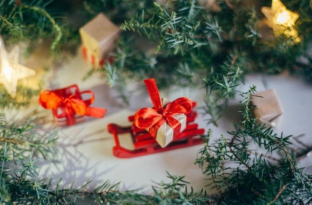 Feliz navidad y felices fiestas tarjeta de felicitación, marco, banner. año nuevo 2020. ramas de los árboles de hoja perenne. caja de regalo de navidad en trineos de madera. caja con una cinta roja.