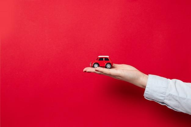 Feliz navidad y felices fiestas tarjeta de felicitación o banner web. mano femenina con una camisa azul sostiene un modelo de automóvil rojo sobre un rojo oscuro con espacio de copia