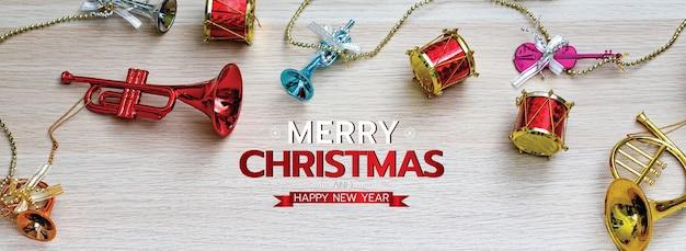 Feliz navidad y feliz año nuevo banner para la cabeza o portada del sitio web de redes sociales o página de fans decorativa. juguetes de adorno de instrumentos musicales para el festival de navidad sobre fondo de madera con textos.