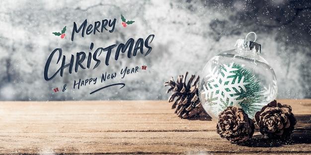 Feliz navidad y feliz año nuevo cartel con adorno de árbol de navidad y cono de pino en mesa de madera con muro de hormigón para celebrar el fondo de la tarjeta de felicitación navideña