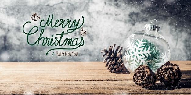 Feliz navidad y feliz año nuevo cartel con adorno de árbol de navidad y cono de pino en mesa de madera