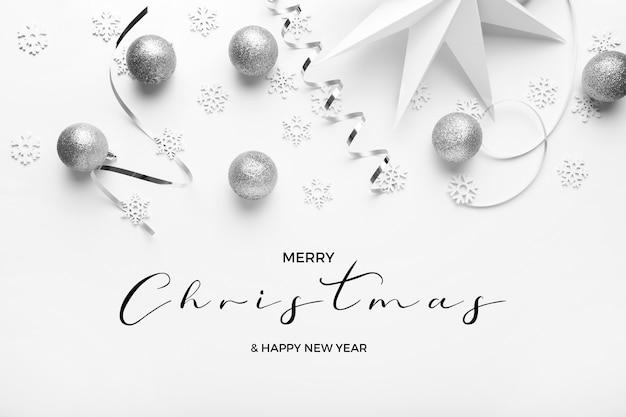 Feliz navidad y feliz año nuevo greetins con tonos plateados sobre un fondo blanco elegante