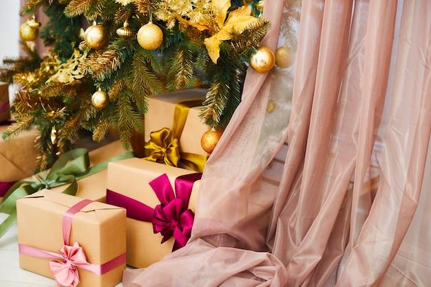 ¡feliz navidad y feliz año nuevo! muchos regalos debajo del árbol de navidad decorado con juguetes de oro. cajas decoradas con regalos debajo del árbol navideño en interiores