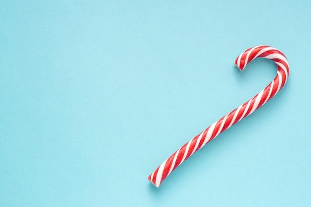 Feliz navidad y feliz año nuevo tarjeta de felicitación. dos bastones de caramelo sobre fondo azul con copyspace para su texto.