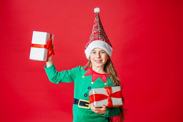 Feliz navidad, feliz chica atractiva con regalos en un disfraz de duende ayudante de santa claus