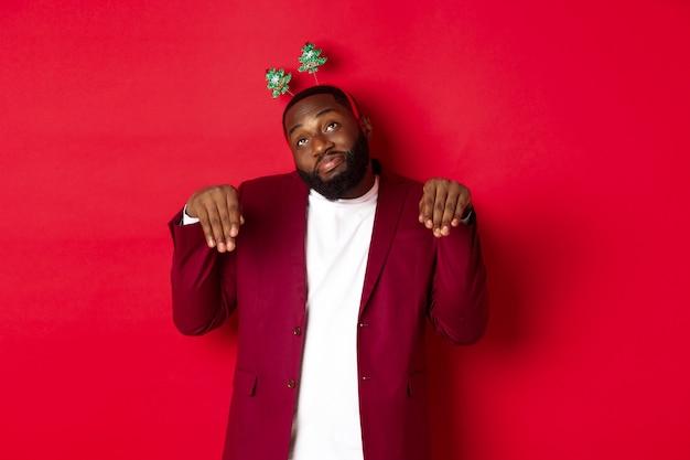 Feliz navidad. hombre negro tonto y divertido en diadema de fiesta, imitando conejito o lindo cachorro, de pie sobre fondo rojo.