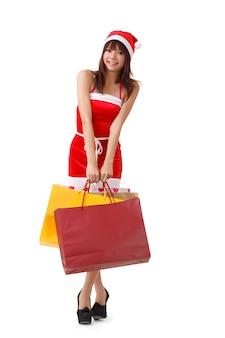 Feliz navidad niña sosteniendo bolsas de la compra.