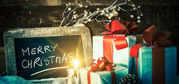 Feliz navidad en una pizarra con regalos y velas.