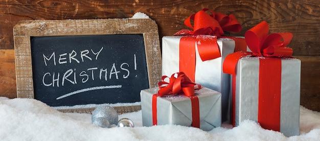 Feliz navidad en una pizarra con regalos, vista panorámica.