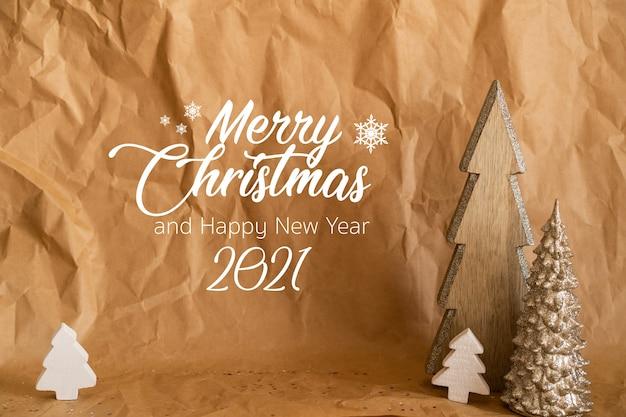 Feliz navidad y próspero año nuevo 2021. papel artesanal con árboles de navidad de madera