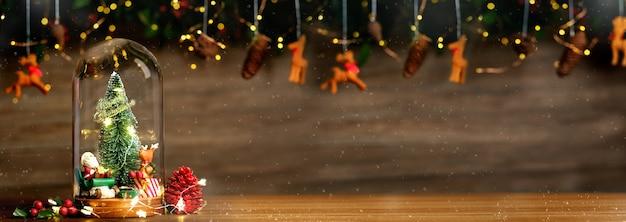 Feliz navidad y próspero año nuevo árbol de navidad y papá noel en decoración de cúpula de vidrio con renos de chuchería, oropel de cono de pino en el fondo de madera espacio para banner de mesa para mostrar el producto