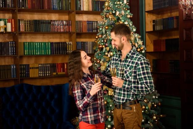 ¡feliz navidad y próspero año nuevo! atractiva pareja joven está celebrando vacaciones en casa juntos, bebiendo champán y sonriendo.
