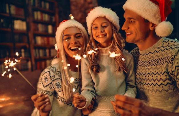 ¡feliz navidad y próspero año nuevo! familia feliz celebrando las vacaciones de invierno en casa. los padres y su hija esperando la navidad con gorro de papá noel con bengalas en las manos.
