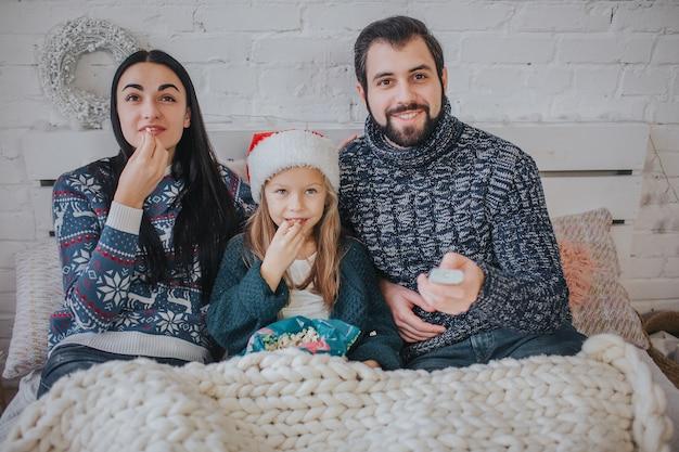 Feliz navidad y próspero año nuevo . familia joven celebrando vacaciones en casa. el padre sostiene el control remoto del televisor. papá, hija y madre están viendo televisión.
