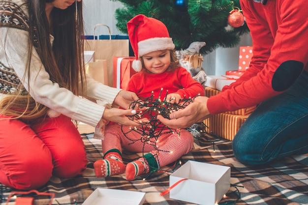 Feliz navidad y próspero año nuevo. una niña pequeña y satisfecha se sienta entre los padres y mira las luces navideñas que los adultos sostienen en las manos. hay una caja blanca y una cinta roja.