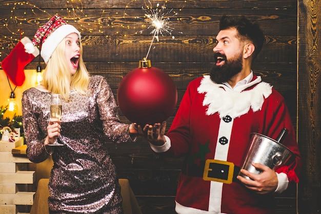 Feliz navidad y próspero año nuevo. pareja de moda sobre las luces del árbol de navidad. sensual