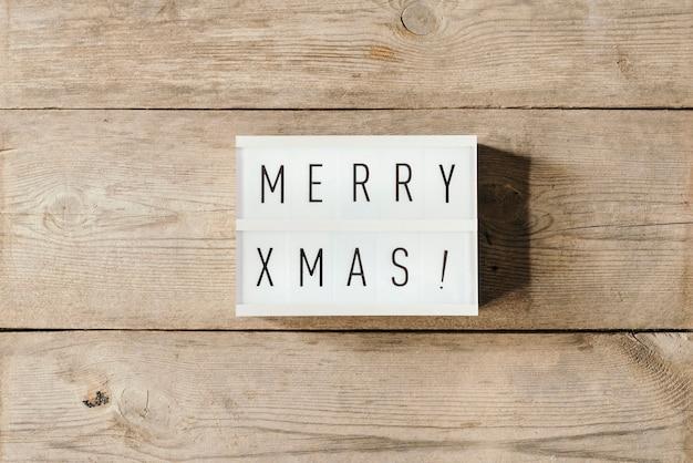 Feliz navidad texto sobre un panel led y fondo de madera