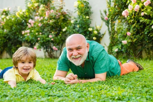 Feliz nieto de la familia abraza a su abuelo en vacaciones feliz abuelo y nieto relajarse juntos c ...