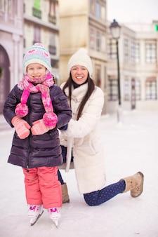 Feliz niña adorable y joven madre patinando sobre hielo