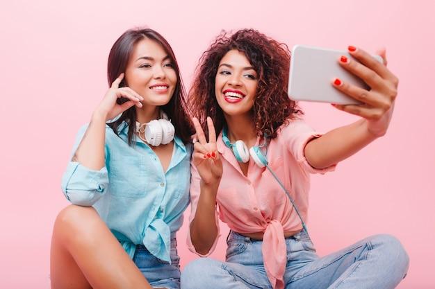 Feliz niña africana con cara bonita posando con el signo de la paz junto a una encantadora amiga. aforable mujer mulata en jeans y camisa rosa haciendo selfie con elegante dama hispana.