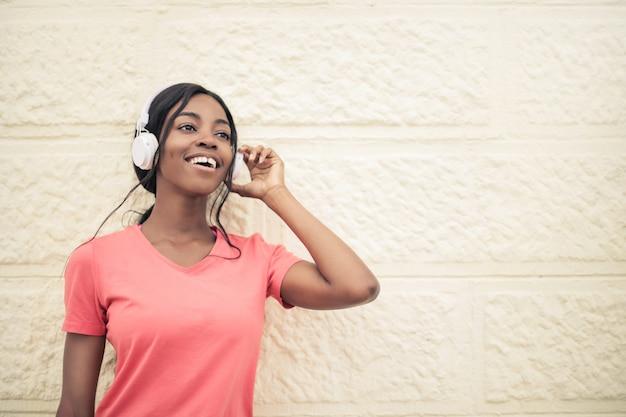 Feliz niña afro escuchando musica