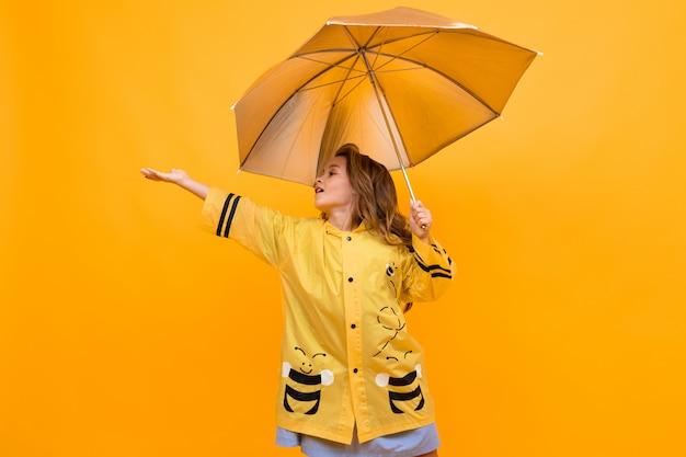 Feliz niña alegre en un hermoso impermeable amarillo con la imagen de una abeja sostiene un paraguas plateado y extiende su mano sobre amarillo