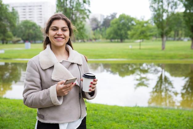 Feliz niña alegre con teléfono disfrutando de un café para llevar