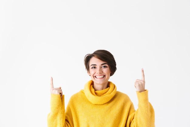 Feliz niña alegre vistiendo sudadera con capucha que se encuentran aisladas en blanco, señalando con el dedo en el espacio de copia