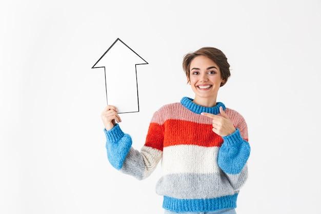 Feliz niña alegre vistiendo suéter de pie aislado en blanco, apuntando hacia arriba con una flecha de papel
