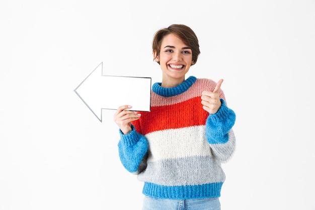 Feliz niña alegre vistiendo suéter de pie aislado en blanco, apuntando con una flecha de papel