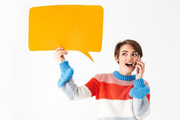 Feliz niña alegre vistiendo suéter de pie aislado en blanco, sosteniendo el bocadillo de diálogo vacío, hablando por teléfono móvil