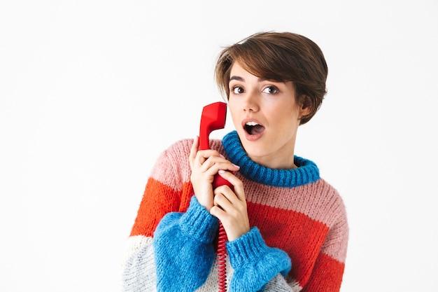 Feliz niña alegre vistiendo suéter que se encuentran aisladas en blanco, hablando por un teléfono fijo