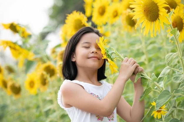 Feliz niña asiática divirtiéndose entre girasoles en flor bajo los suaves rayos del sol.