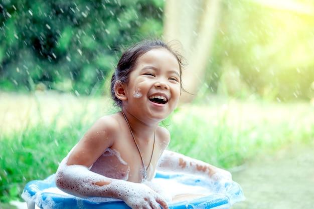 Feliz niña asiática divirtiéndose y jugando con espuma
