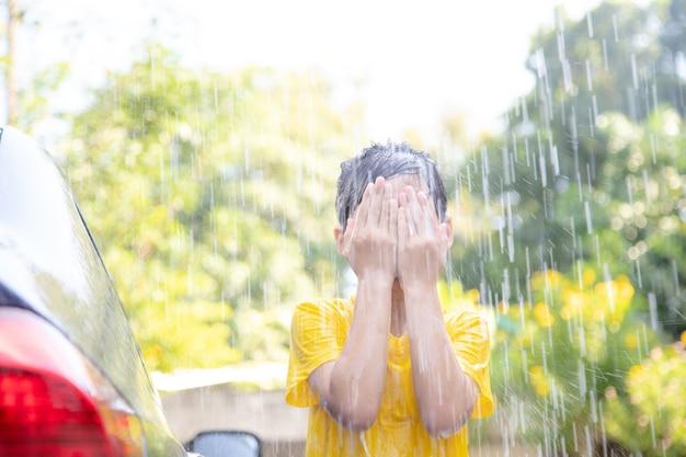 Feliz niña asiática lavando el coche en las salpicaduras de agua y la luz del sol en casa