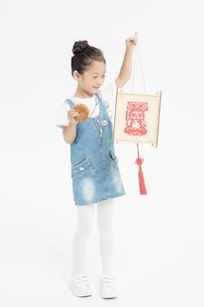 Feliz niña asiática con linterna y pastel de luna