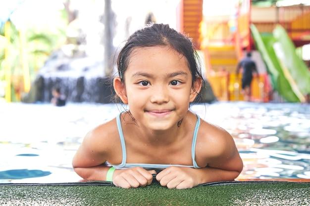 Feliz niña asiática en la piscina
