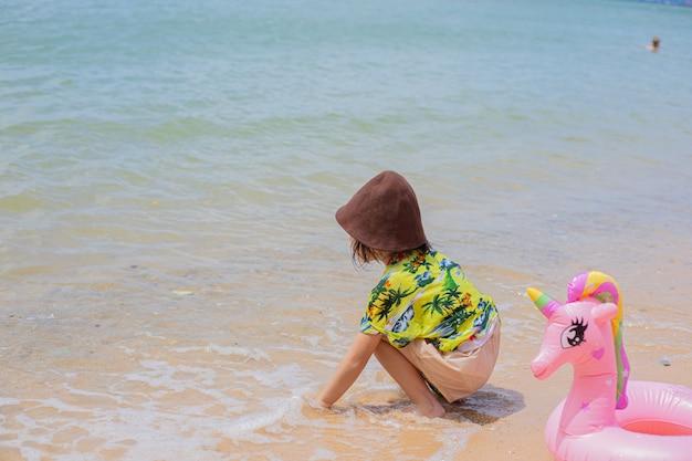 Feliz niña asiática en la playa.