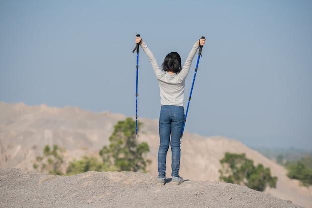 Feliz niña asiática senderismo en las montañas de pie sobre una cresta rocosa cumbre y un poste con vistas al paisaje.