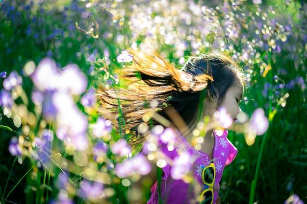 Feliz niña asiática en serpiente con cresta campo de jardín de flores de color púrpura dulce