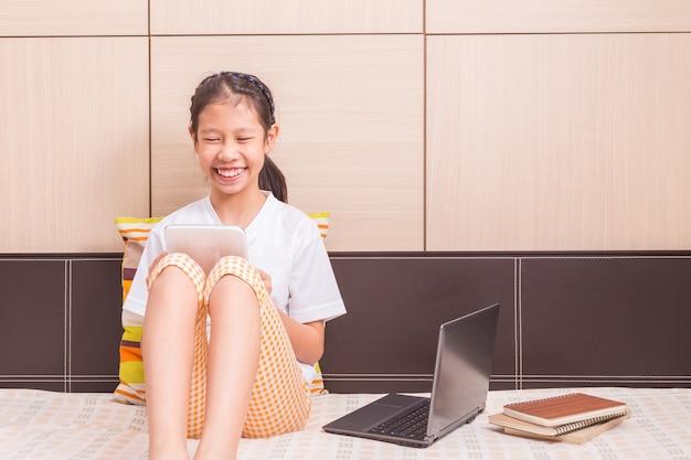 Feliz niña asiática sonriente con tablet pc para estudiar en su cama