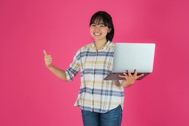 Feliz niña asiática sonriente con el uso de la computadora portátil sobre fondo rosa