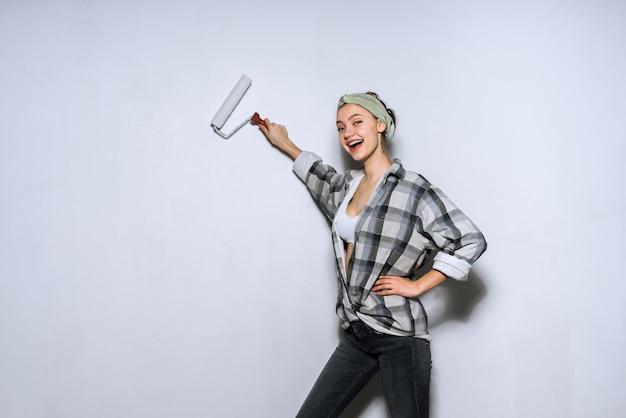 Feliz niña en camisa a cuadros colorea la pared con un rodillo en blanco