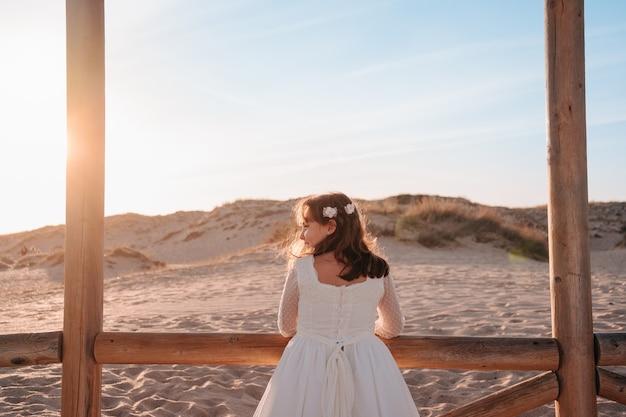 Feliz niña caucásica apoyado en un poste mirando a la playa