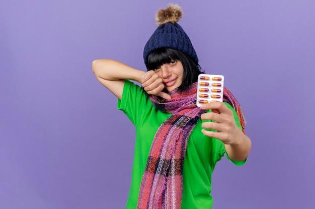 Feliz niña caucásica enferma joven con gorro de invierno y bufanda que se extiende paquete de cápsulas mostrando el pulgar hacia arriba mirando a cámara aislada sobre fondo púrpura con espacio de copia
