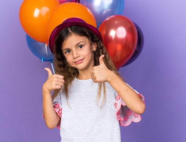 Feliz niña caucásica con sombrero de fiesta violeta pulgar arriba de pie delante de globos de helio aislado en la pared púrpura con espacio de copia