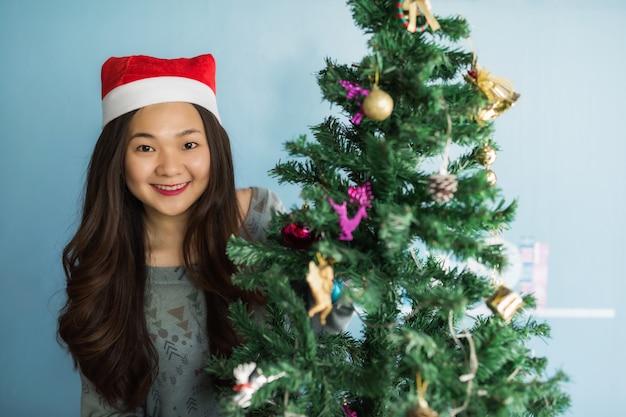 Feliz niña china asiática en el árbol de navidad