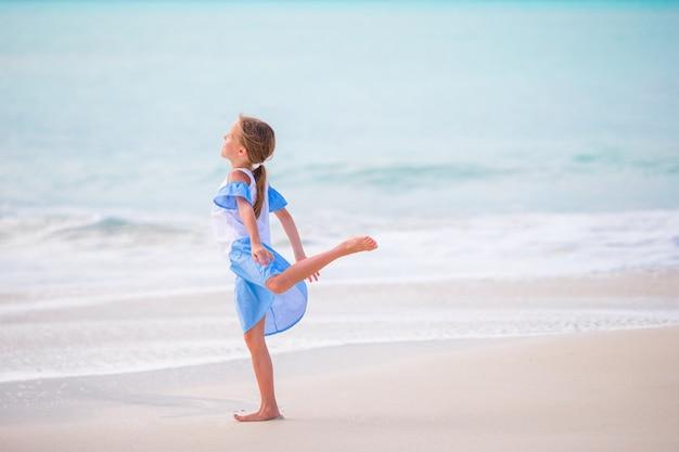 Feliz niña disfruta de fondo de vacaciones de verano el cielo azul y el agua turquesa en el mar