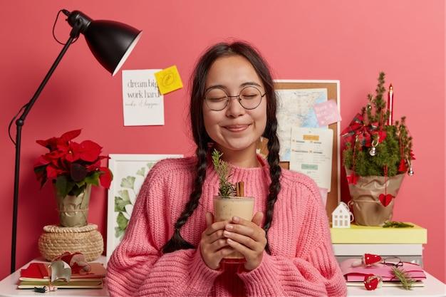 Feliz niña encantadora con dos largas trenzas, mantiene los ojos cerrados, bebe cóctel de ponche de huevo fresco, disfruta del invierno y las vacaciones, usa gafas y suéter, fondo rosa con navidad