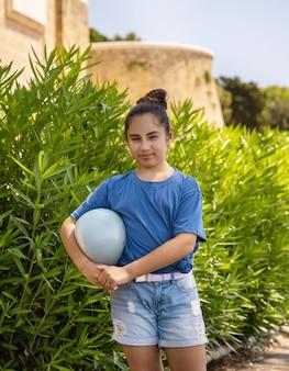 Feliz niña escolar en camiseta azul sosteniendo la pelota al aire libre maqueta de camiseta